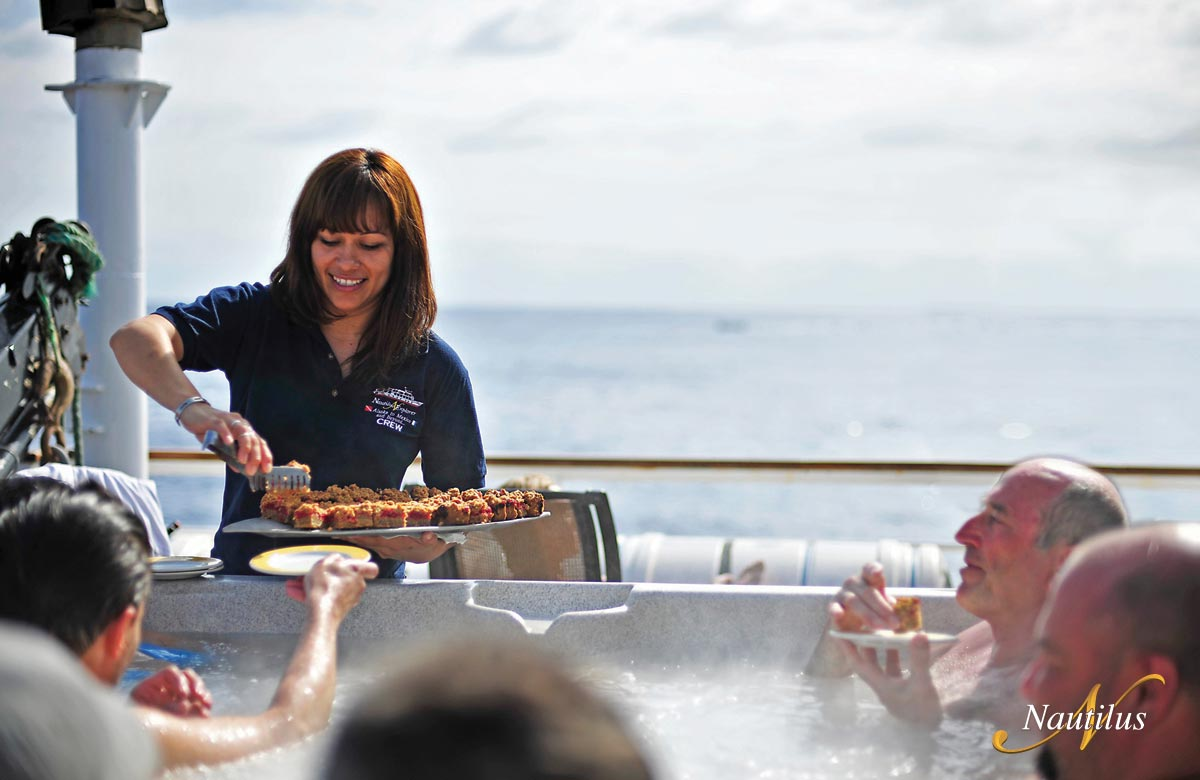 Hostess serving food to guests in the Hot Tub on the Nautilus Explorer