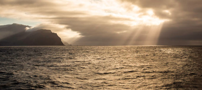 golden crepuscular rays shining down on the socorro islands