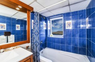 Relax in the deep blue bathroom in the Emerald Suite onboard the Nautilus Explorer