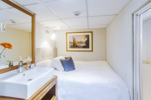 Stateroom B onboard the Nautilus Explorer features a large bed and extra storage space