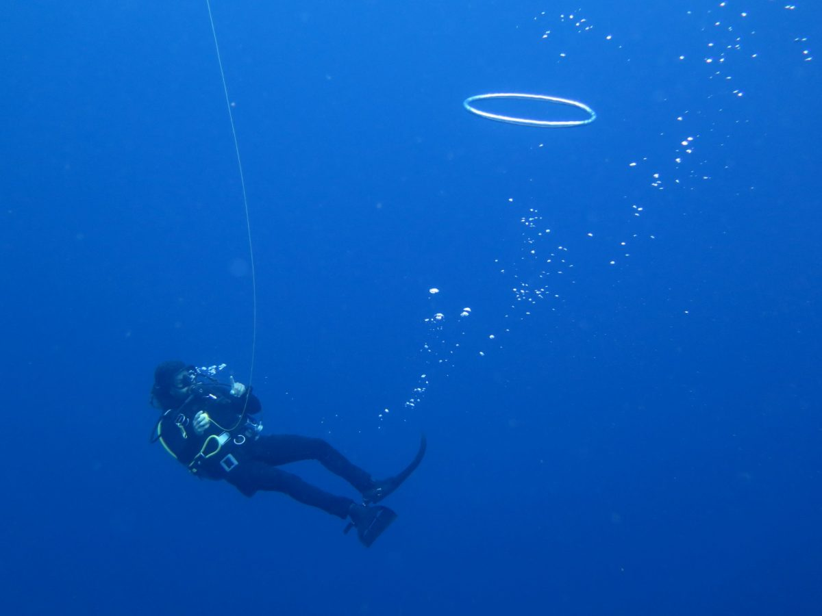 diver floats and plays with regulator bubbles