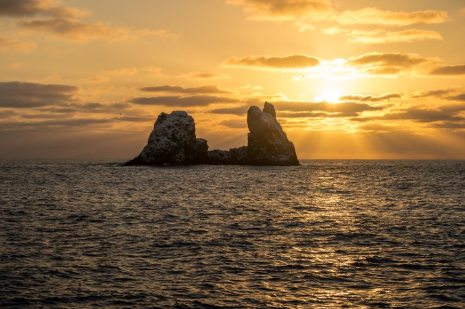 a warm sunset shining on roca partida, the split rock